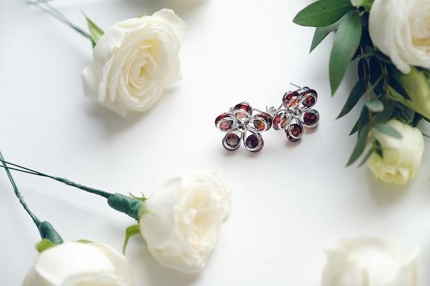 花嫁のイヤリング。白いバラの近く。結婚式の道具とアクセサリー。