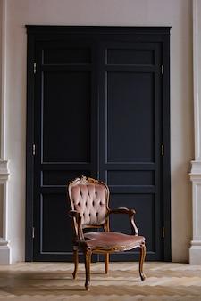 リビングルームの黒いドアに対してベージュ色のベロア椅子。レトロなスタイルの部屋のインテリア。