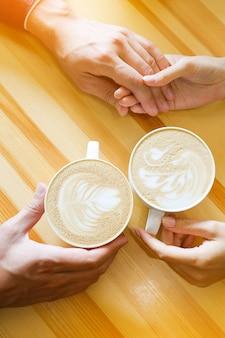 カフェ、恋人たちの手で手を繋いでいるカップル。男と女のコーヒーのマグカップを保持しています。