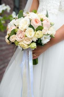 花嫁の手の中にピンクと白の花の花束。
