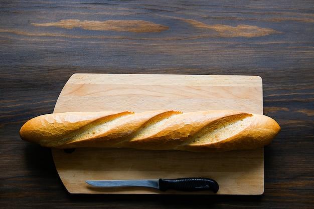 Свежеиспеченный хлеб, кухонный нож с черной пластиковой ручкой, разделочная доска на деревянном столе.