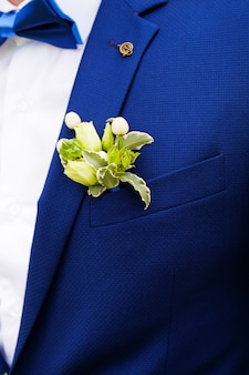 白いシャツ、蝶ネクタイ、青いベストまたはジャケットの若い男性または新郎。ベストポケットまたはラペルの白いバラと緑の葉の美しいブートニア。結婚式のテーマ。