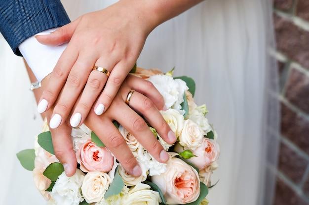 結婚式のブーケに新郎新婦の手。