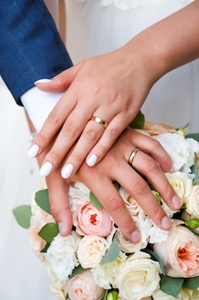 Руки жениха и невесты на свадебный букет.