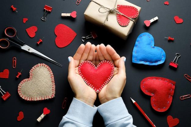 Красное сердце или валентина в руках девушки, на черном фоне. фон дня святого валентина. красные и синие скрепки, прищепки, подарки, валентинки, ленты, карандаши. концепция ручной работы