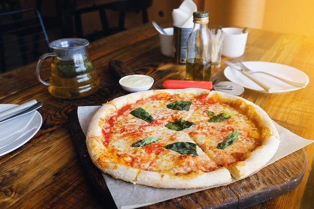 木の板にモッツァレラチーズ、トマト、スパイス、新鮮なバジルのベジタリアンイタリアピザマルガリータ。