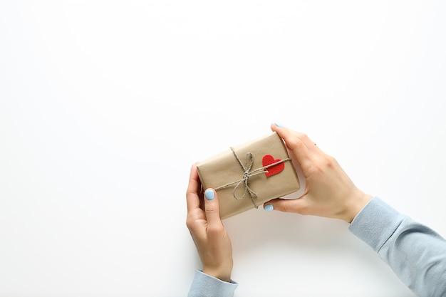 Женские руки держат подарок в оберточной бумаге, на день святого валентина. красная декоративная сердечная валентинка или на упаковке. ручной работы.