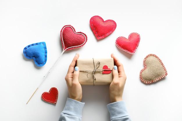 Женские руки держат подарок в оберточной бумаге, на день святого валентина. красные и синие декоративные валентина и сердца. ручной работы.