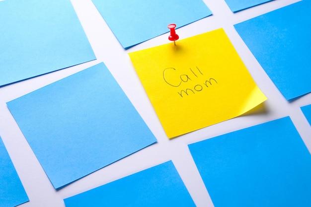 情報を思い出させるための黄色のスティッキーステッカーに「お母さんに電話してください」というメッセージとペーパークリップが添付されています