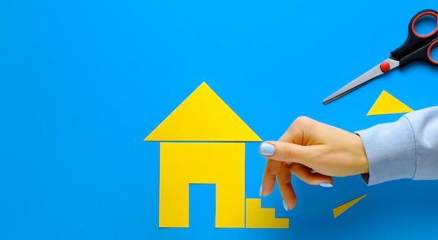 色紙で切り取られた家。女性の指が階段を上っていきます。家を所有し、住宅を購入し、建築するという夢を実現するというコンセプト。バナー。