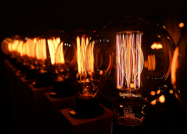 Ряд ретро эдисон стеклянные лампы на темном фоне, крупным планом. дизайнерский свет и освещение в интерьерах. выборочный фокус.