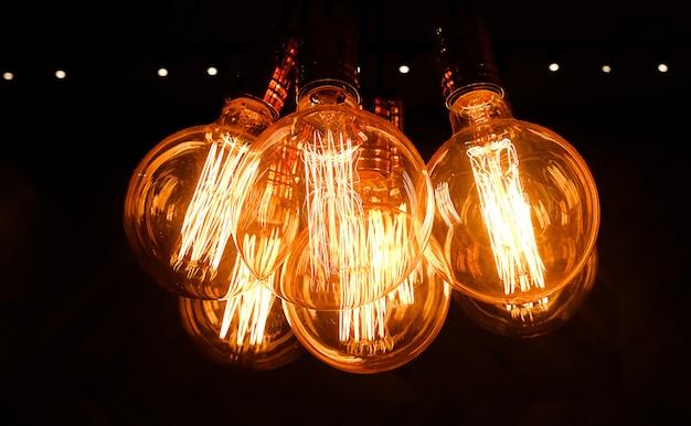 Стеклянные ретро эдисон лампы на темном фоне, крупным планом. дизайнерский свет и освещение в интерьерах. выборочный фокус.