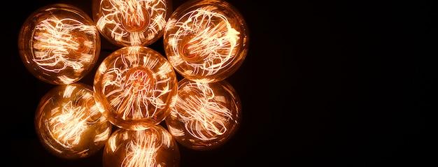 暗い背景にガラスレトロエジソンランプクローズアップ。インテリアのデザイナーライトと照明。セレクティブフォーカス。バナー