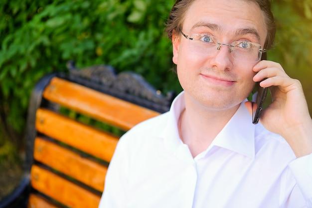 Мужской менеджер, фрилансер, бизнесмен в очках, работающих на открытом воздухе. общается, разговаривает по мобильному телефону, улыбается.