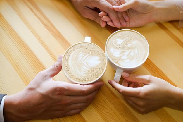 コーヒーを飲みながらカフェで手を繋いでいるカップル、木製のテーブルの背景に恋人たちの手。婚約、男は彼の女の子の手を握る。写真は粒状感とノイズで覆われています。