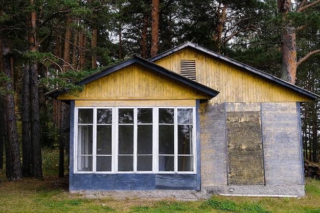 大きな窓のある美しい夏のカントリーハウス。ひびの入った塗料を使用した森の中の古い平屋建ての建物。着色写真。