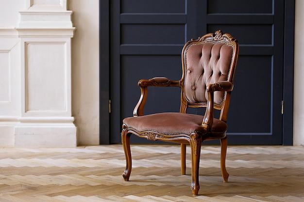 リビングルームの黒いドアに対するベージュのベロア椅子。レトロなスタイルの部屋のインテリア。