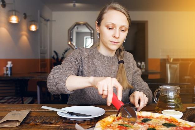 女の子はモッツァレラチーズ、トマト、スパイス、新鮮なバジルでベジタリアンピザをカットします。おいしいイタリア料理。木の板にピザマルガリータをスライスしました。閉じる。おいしいランチ、スナック
