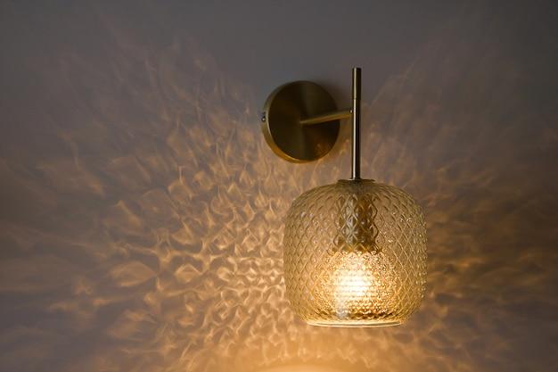 壁に古典的なクリスタルの壁取り付け用燭台またはランプ、ライトが点灯している壁紙の背景。テキスト用のスペースをコピーします。セレクティブフォーカス。