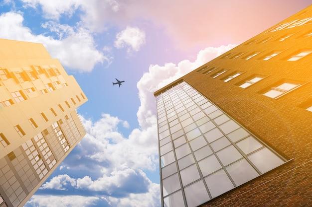 雲の背景にある新しいレンガ造りの多階建ての建物。空を飛んでいる飛行機。着色写真。