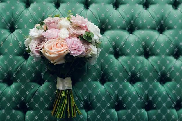 Красивый свадебный букет на фоне роскошного велюра, крупным планом. букет из разных цветов и зеленых листьев, перевязанный атласной лентой, размытый фон. свадебная тема.