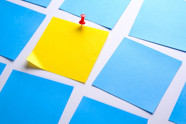 情報を思い出させるための白い背景に黄色の付箋ステッカー、ペーパークリップが添付されています。テキスト用のスペース。隣には空の青いステッカーがあります。