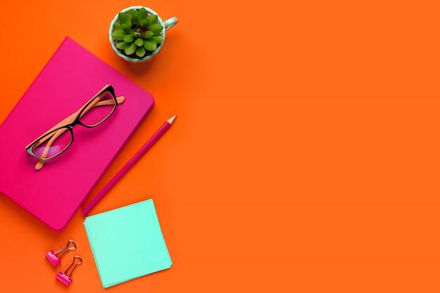 Очки лежат на розовом блокноте рядом с карандашом на фоне пышной лавы. рядом с карандашом, наклейки, скрепки и цветок. рабочее место фрилансер, предприниматель, предприниматель.