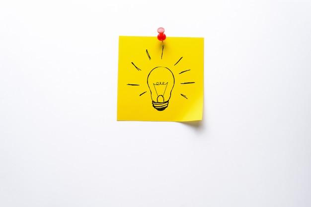 Творческий рисунок лампочки на желтой наклейке. концепция новых идей, инноваций, решения проблем.