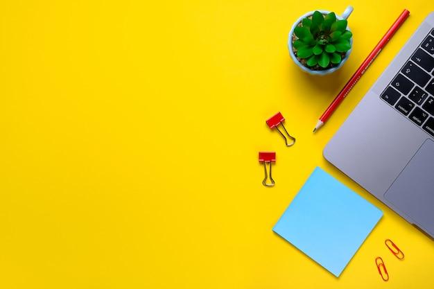 ノートパソコン、花、ステッカー、ペーパークリップ、黄色の背景にひな形。職場のフリーランサー、ビジネスマン、起業家、ビジネスウーマン。バナー。