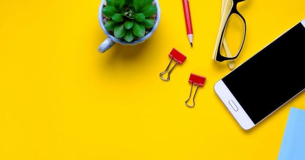 メガネ、携帯電話、花、ステッカー、ペーパークリップ、黄色の背景にひな形。職場のフリーランサー、ビジネスマン、起業家。バナー