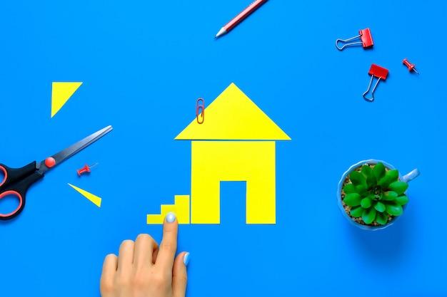 色紙で切り取られた家。女性の指は階段を取り付けます。自分の家の夢を実現し、住宅を購入して建築するというコンセプト。