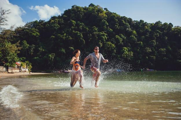 山々と青い海の水と空、屋外のビーチの海岸に沿って走って一緒に手を取り合って美しい観光若いカップルが水しぶきを作成します。ライフスタイル旅行・観光、新婚旅行