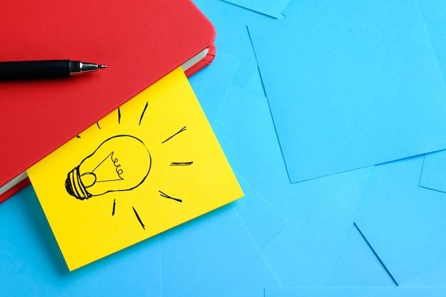 赤いメモ帳に添付された黄色のステッカーに電球の創造的な図面。隣にペンがあります。新しいアイデア、イノベーション、問題の解決策のコンセプト。