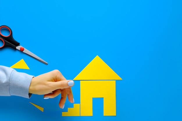 色紙で切り取られた家。女性の指が階段を上っていきます。家を所有し、住宅を購入し、建築するという夢を実現するというコンセプト。