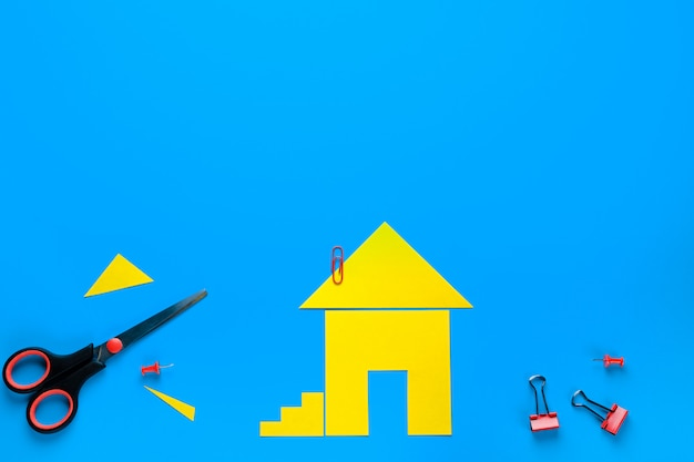 色紙で切り取られた家。はさみが近くにあります。家を所有し、購入し、家を建てるという夢を実現するというコンセプト。