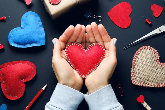 黒い背景に、少女の手の中のバレンタイン。赤と青のハート、はさみ、文房具があります。バレンタインデーの背景。手作りのコンセプト。