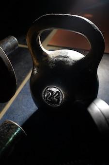 暗い部屋で古くて重いケトルベルの重さ。