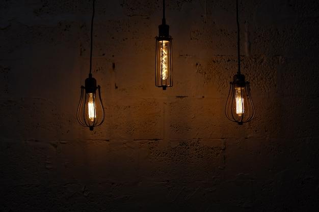 ガラスのレトロ電球エジソンと暗い背景。