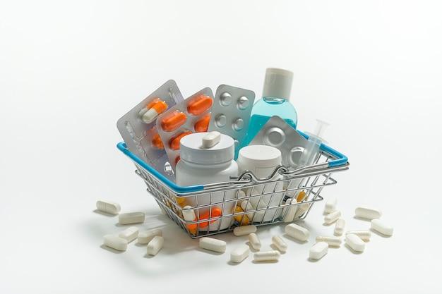 タブレットと白い背景の上のショッピングカートの薬。広告のレイアウト。薬と薬局のコンセプト。