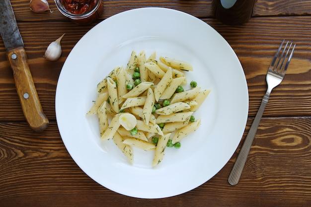 ペストソース、グリーンピース、ニンニク、ディルの木製テーブルの上の皿にパスタ。イタリア料理。