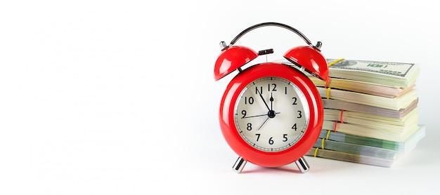 紙のドルとユーロの山にレトロなスタイルの真っ赤な目覚まし時計。時は金なり。事業コンセプト。