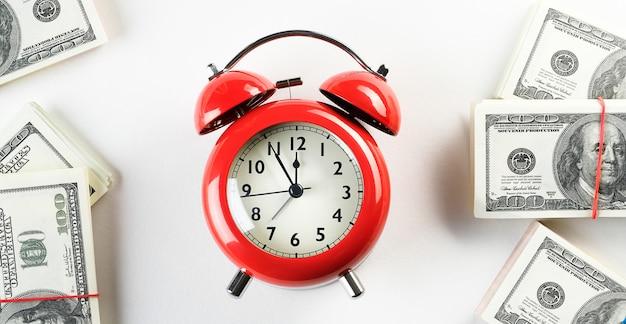 Ярко-красный будильник в стиле ретро на кучу бумажных долларов и евро. время - деньги. бизнес-концепция