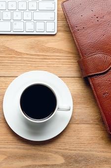 Клавиатура компьютера, блокнот для заметок, чашка кофе или чая, на деревянном столе.