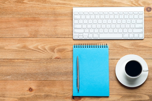 Компьютерная клавиатура, ручка и блокнот для заметок, чашку кофе или чая, на деревянном столе.