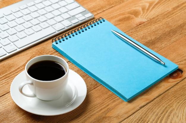 Клавиатура компьютера, блокнот и тетрадь для заметок, чашку кофе или чая, на деревянном столе. темы работы бизнесмена или менеджера на рабочем месте.