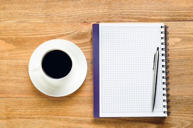 Ручка на чистом листе блокнота и кружка черного кофе на деревянном столе. предметы бизнесмена или менеджера на рабочем месте.