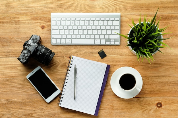 Мобильный телефон, клавиатура компьютера, ручка и блокнот для заметок, кружка кофе, флэш-накопители и камеры на деревянном столе.
