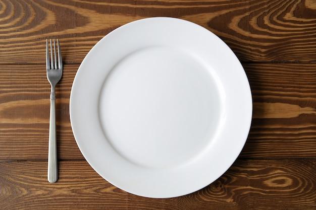 木製のテーブルに空の白い皿をクローズアップ。フォークの隣に横になっています。食品の概念