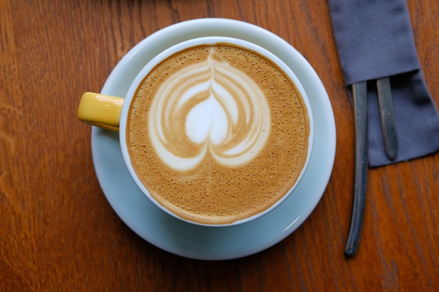 カフェの木製テーブルの上の青い受け皿にカプチーノカップ。近くにはカトラリーがナプキンに入っています。コーヒーブレイク