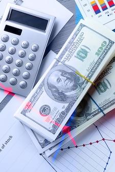 机の上のチャートとヒストグラム、お金と電卓